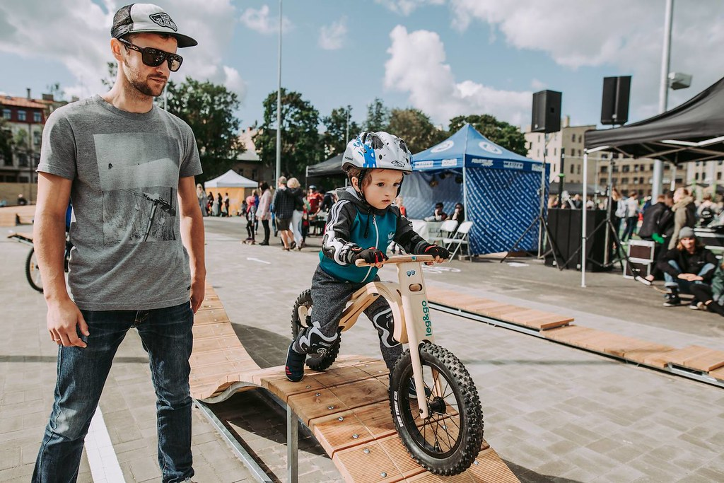 A younster (or future pro) tries out the wooden skills course next to the pumptrack at center sports square in Riga, Latvia