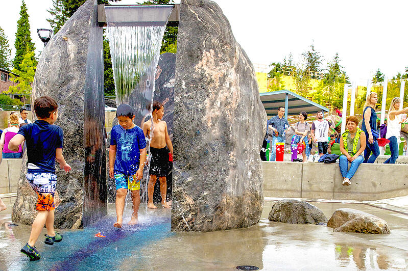 """A boy walks through the waterfall feature between two """"boulders"""" at universally accessible Inspiration Park in Bellevue, WA, USA."""