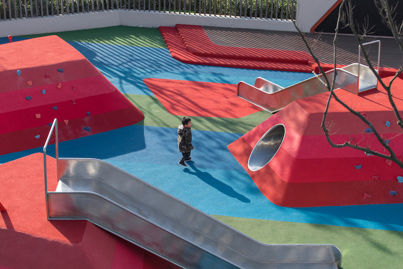 A child plays in Pomegranate Place playground, a multigenerational playground where adults and children meet, relax and socialize.