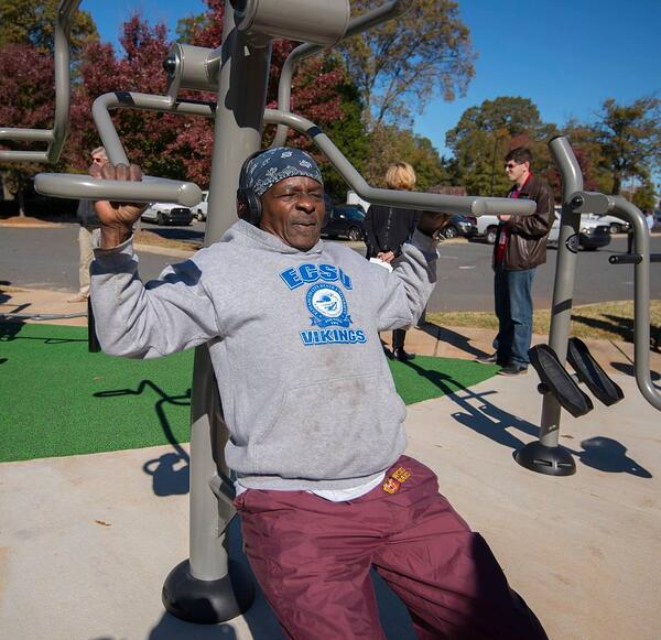 A patron makes use of the outdoor fitness equipment at Marion Diehl multigenerational playground in Charlotte, NC.