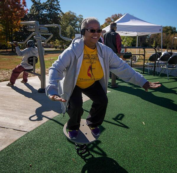 A patron smiles while balancing on a feature at Marion Diehl multigenerational playground in Charlotte, NC.