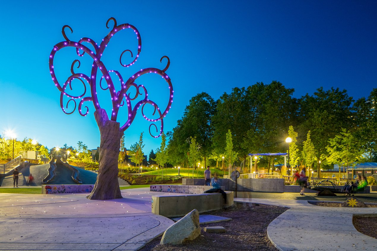 A whimsical looking tree lights up at night at Inspiration Playground, providing sensory delight. The playground is universally accessible and located in Bellevue, WA, USA.