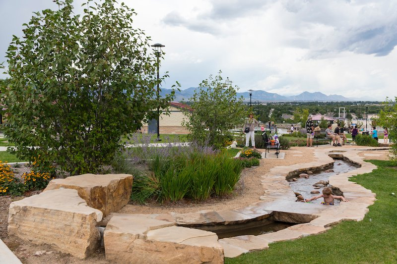 Children and adults alike can enjoy the water play area of Discovery Park's multigenerational playground in Wheat Ridge, CO.