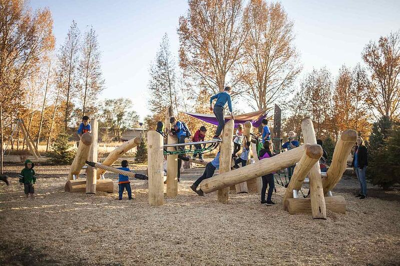 Children climb over logs and the rest of the natural playground at Rio Grande Farm Park