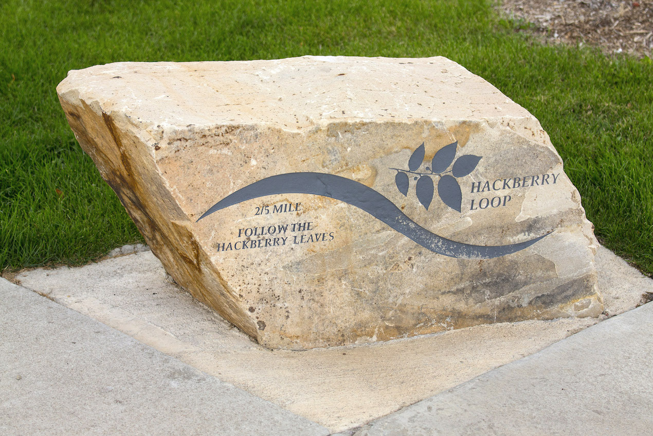 An artistic marker etched in natural stone along an accessible path at Discovery Park's multigenerational playground.