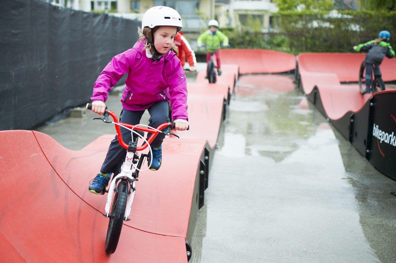 Child riding a PARKITECT modular pumptrack.