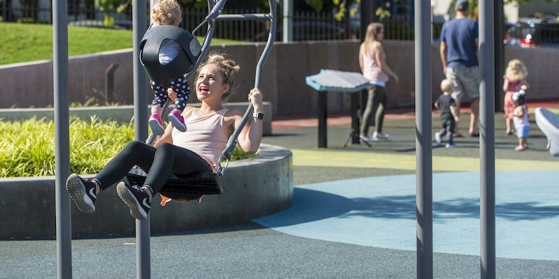 A woman enjoys the two-way swing with a baby at Let's All Play Park, a multigenerational park located at Salem Health Hospital in Salem, OR, USA.