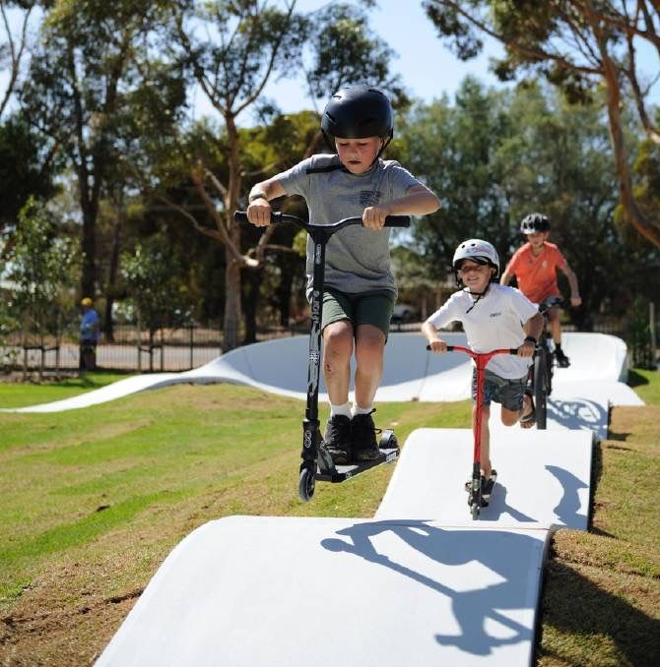 Three kids riding a PARKITECT precast concrete modular pumptrack in Wudinna, Australia