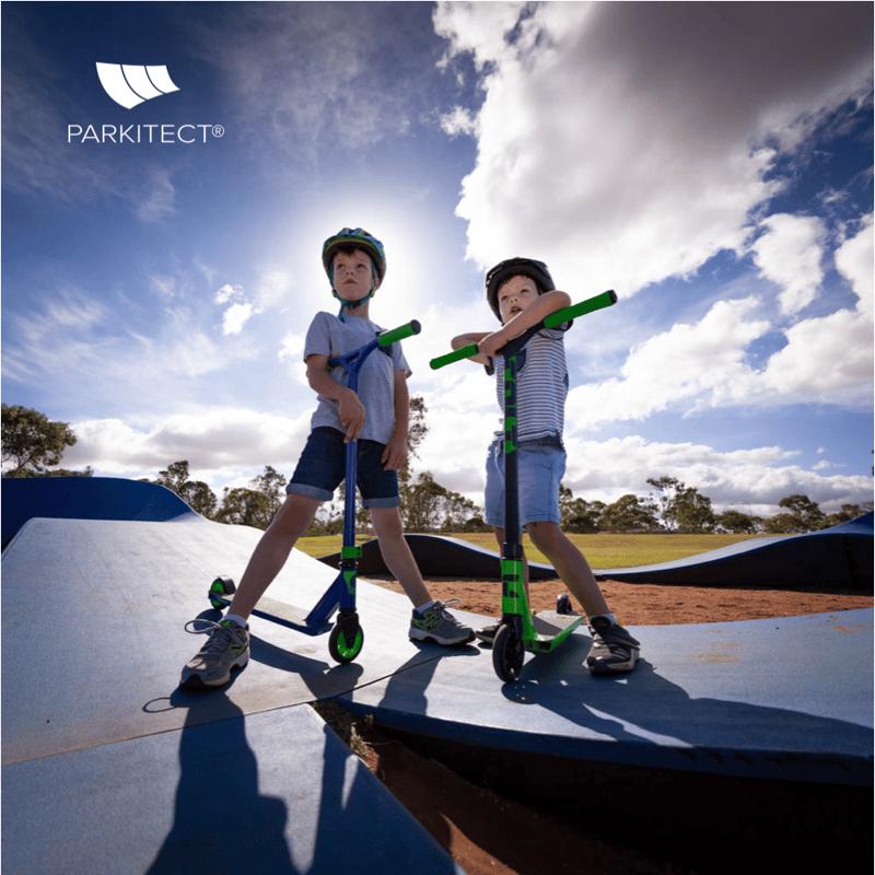 Kids enjoying a PARKITECT modular pumptrack on their razor scooters.
